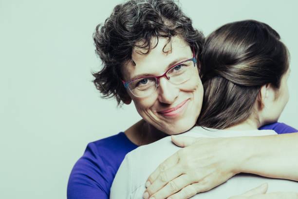 porträt von glücklich senior frau umarmen tochter - emoticon hug stock-fotos und bilder