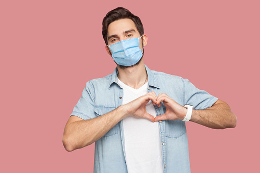 Portrait of happy smiley young man with surgical medical mask in blue shirt standing with love hand gesture on heart and looking at camera smiling. indoor studio shot, isolated on pink background.