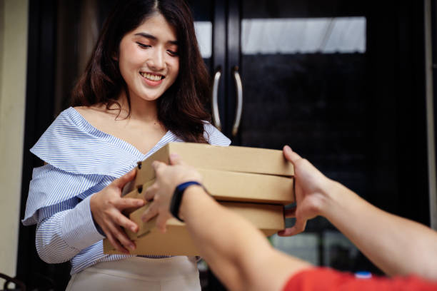 Portrait of happy smiling Asian woman in casual clothing receiving a pizza packaging box from delivery man. Fast food order from customer at home. Food delivery service concept