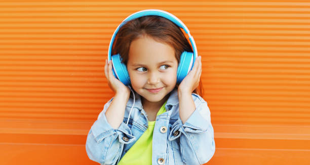 Portrait of happy smiling child in headphones listening to music on city street over orange wall background stock photo
