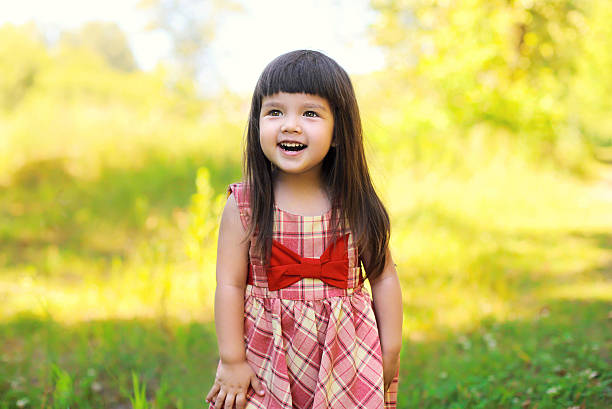 Portrait of happy smiling cute little girl child outdoors stock photo