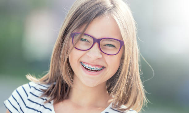 Portrait of happy smiling girl with dental braces and glasses. stock photo