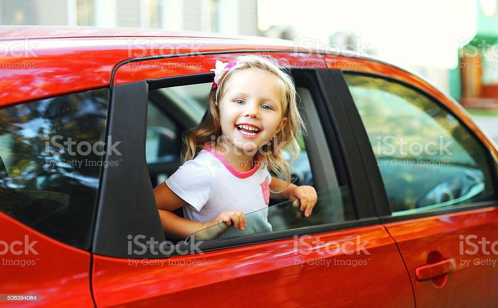 Porträt von glücklich lächelnd kleines Kind sitzt im roten Wagen – Foto