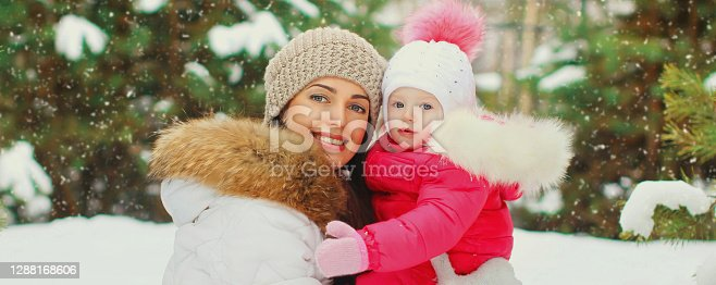 istock Portrait of happy smiling mother and little child in winter day together over snowy background 1288168606