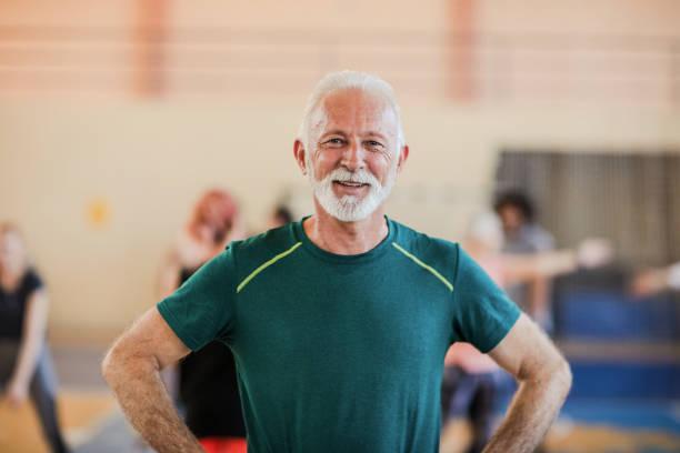 Porträt des fröhlich lächelnden älteren Mannes im Fitnessstudio – Foto