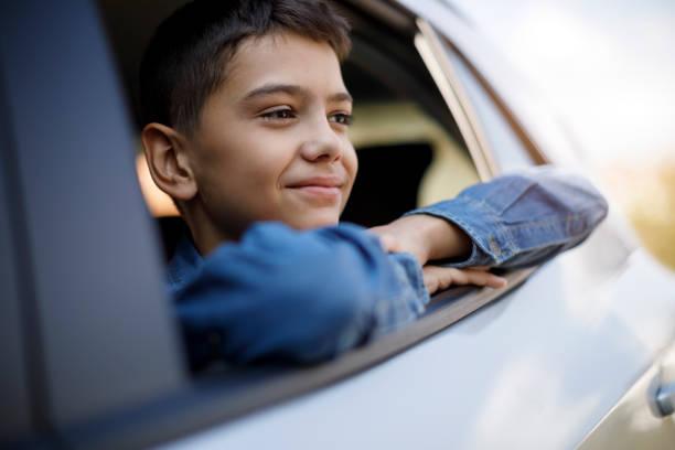 Portrait of happy smiling teenage boy sitting in the car Portrait of happy smiling teenage boy sitting in the car boy looking out window stock pictures, royalty-free photos & images