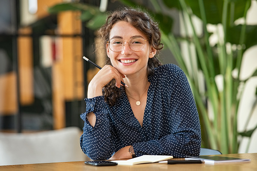 Portrait of smiling woman wearing spectacles and holding pencil while sitting at desk. Business woman taking notes in diary and looking at camera. University girl with eyeglasses sitting on table at library.