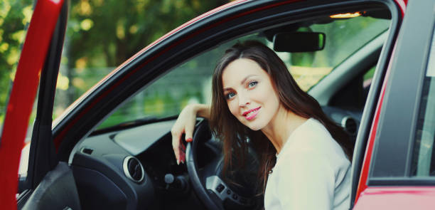 Portrait of happy smiling woman driver behind a wheel red car stock photo