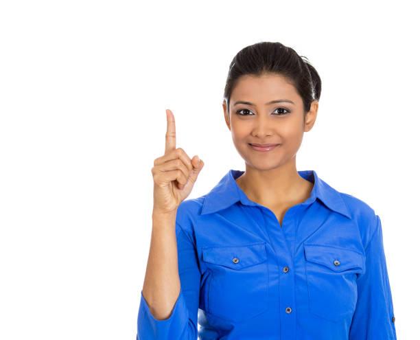 Retrato de una mujer feliz y sonriente, que muestra el dedo índice señalador hacia arriba - foto de stock