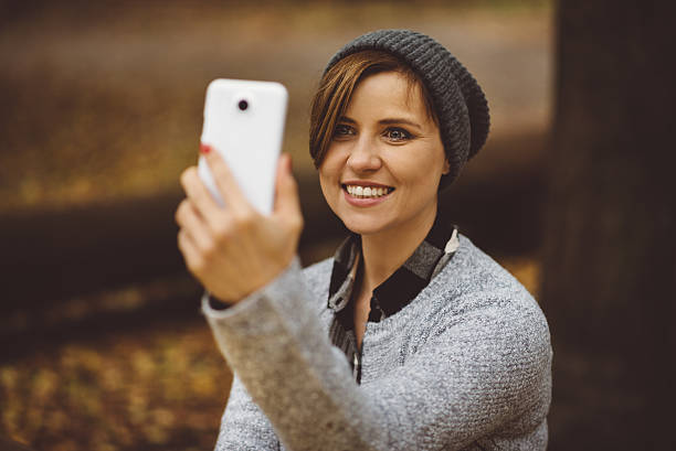 portrait of happy, smiling woman sitting alone in the forest - low contrast stock pictures, royalty-free photos & images