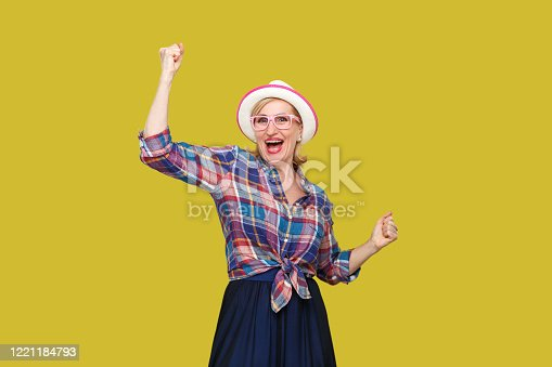 Portrait of happy surprised modern stylish mature woman in casual style with hat and eyeglasses standing and celebrating her victory and looking at camera. studio shot isolated on yellow background.