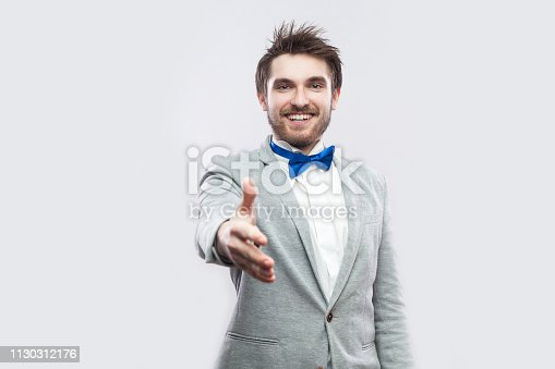 Portrait of happy toothy smiley handsome bearded man in casual grey suit, blue bow tie standing, looking and giving hand to greeting or handshake. indoor studio shot, isolated on light grey background