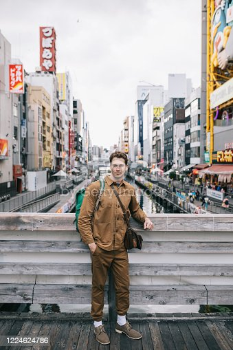 Happy tourist exploring Dotonbori shopping district in Osaka, Japan. Best place to do some shopping and sightseeing