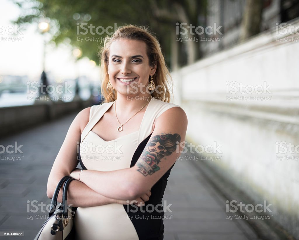 Portrait of happy transgender female with handbag and tattoo stock photo