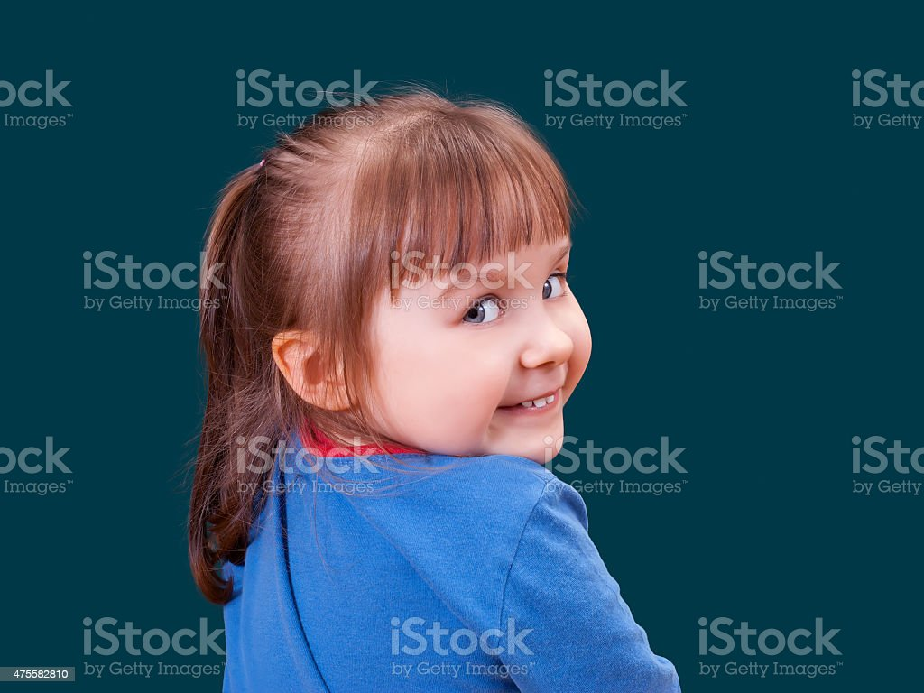 Portrait of happy turning around and smiling little girl stock photo