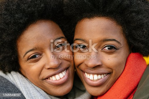A portrait of two happy twin sisters standing in front of a yellow background.