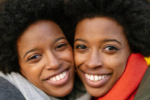 ritratto di sorelle gemelle felici davanti a sfondo giallo - gemelle foto e immagini stock