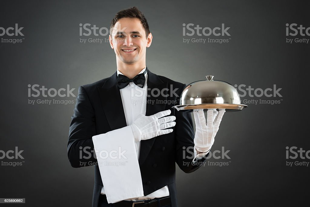 Portrait Of Happy Waiter With Tray And Towel stock photo