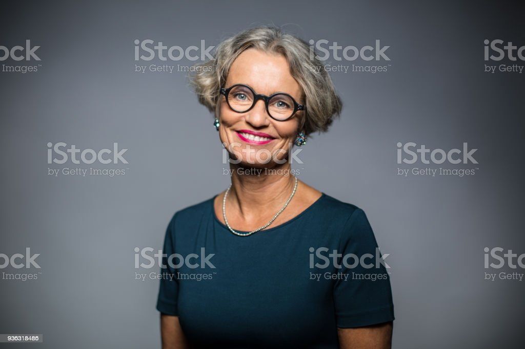 Portrait of happy woman against gray background stock photo