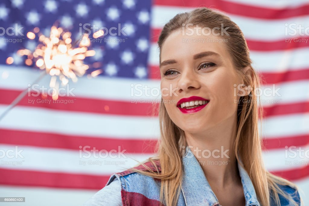 portrait of happy woman holding sparkler with American flag behind stock photo