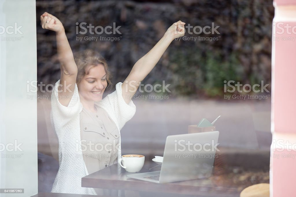 Portrait of happy woman in coffee shop celebrating success with stock photo