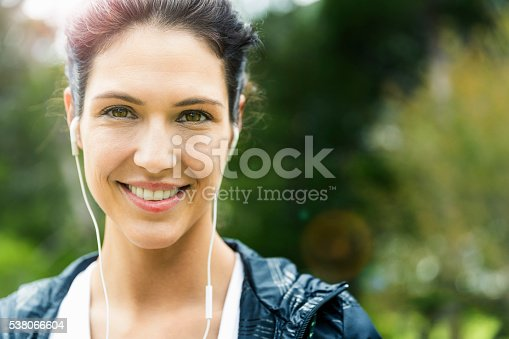 A photo of happy woman wearing earphones. Portrait of beautiful female is enjoying music. She is spending leisure time outdoors.