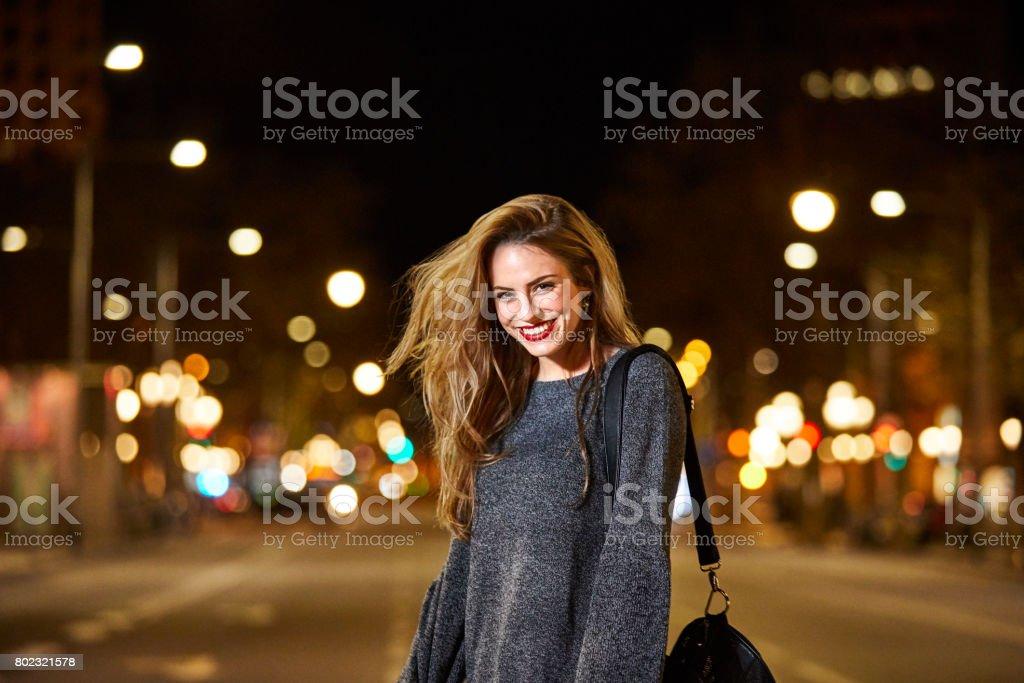 Retrato de uma mulher feliz na estrada na cidade à noite - foto de acervo