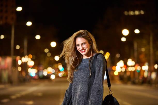 Porträt von glücklich Frau auf der Straße in der Stadt bei Nacht – Foto