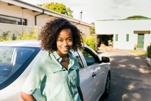 Portrait of happy woman standing by car on street stock photo