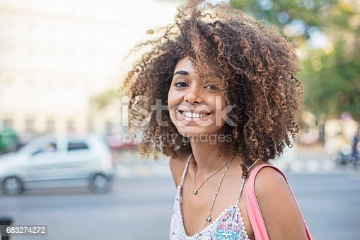 Portrait of happy woman in city. Young smiling female standing outdoors. She is wearing casuals.