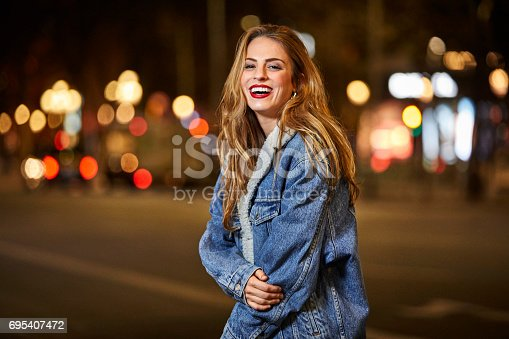 Portrait of smiling young woman standing on street. Cheerful female with brown hair wearing denim jacket. She is in city at night.