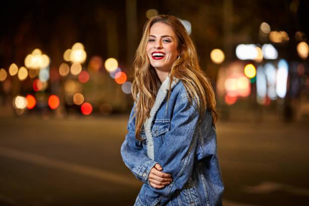 porträt von glücklich frau auf straße in der nacht - lange jacken stock-fotos und bilder