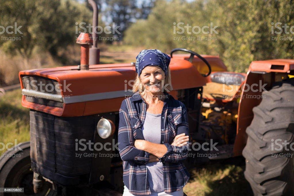 Portrait de femme heureuse debout avec les bras croisés contre tracteur - Photo