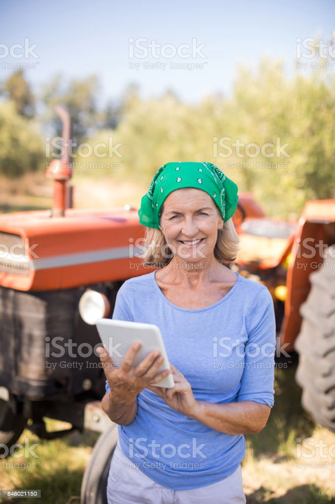 Portrait of happy woman using digital tablet in olive farm stock photo
