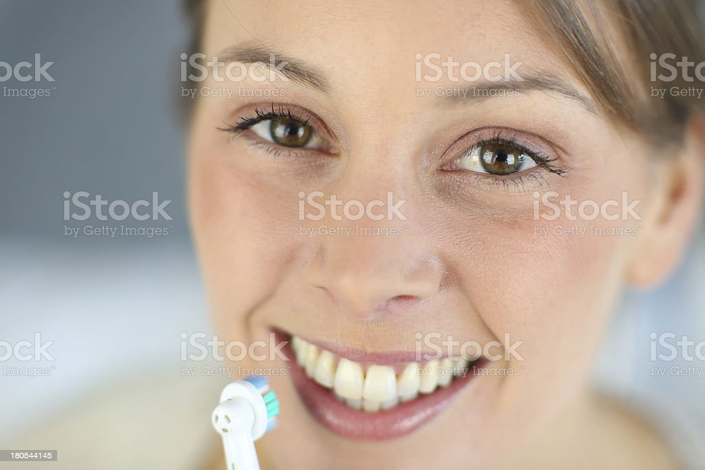 Portrait of happy woman using electric toothbrush royalty-free stock photo