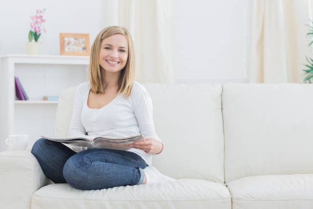 portret van gelukkige vrouw met magazine thuis - woman home magazine stockfoto's en -beelden