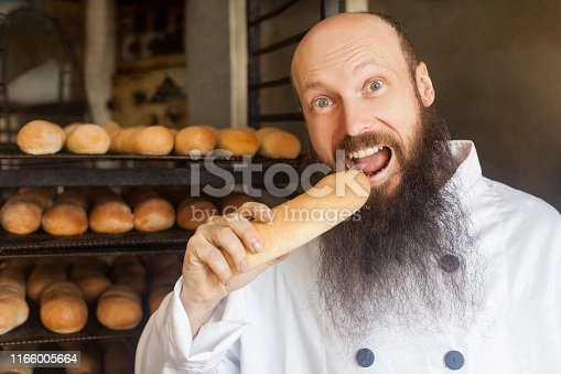 istock Portrait of happy young adult hungry baker with long beard in white uniform standing in his workplace and tasty fresh baked long loaf 1166005664