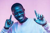 istock Portrait of happy young african man listening to music with wireless earphones isolated on pink background 1090819356