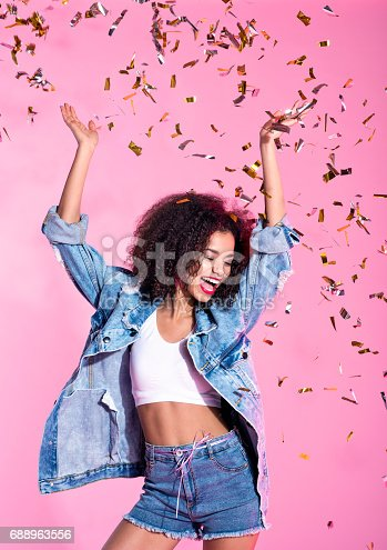 istock Portrait of happy young afro woman among confetti 688963556