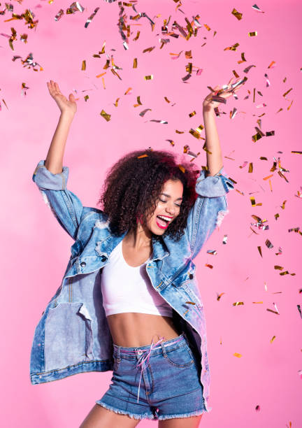 Portrait of happy young afro woman among confetti stock photo