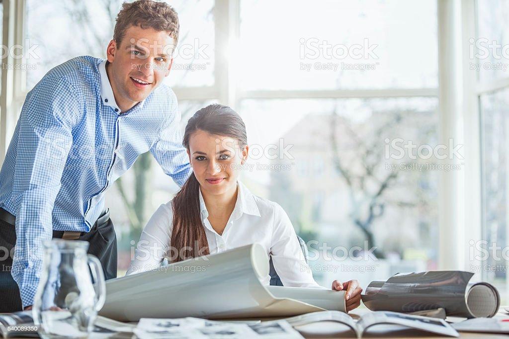 Porträt von glücklichen jungen Architekten mit Blaupausen am Schreibtisch – Foto