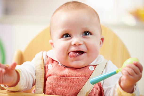 porträt von glücklichen jungen babymode-jungen in hochstuhl - kinderstuhl und tisch stock-fotos und bilder