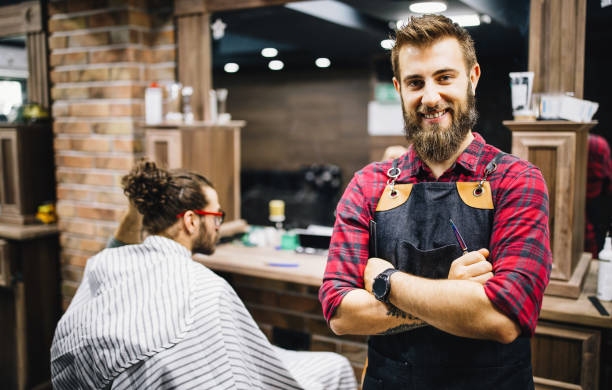Portrait of happy young barber with client at barbershop and smiling. stock photo