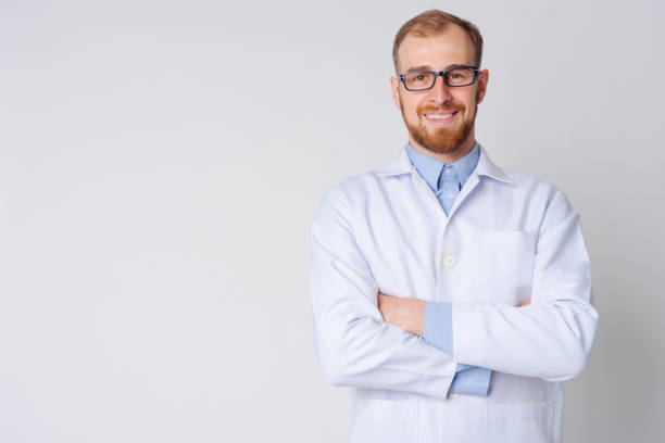 Portrait of happy young bearded man doctor wearing eyeglasses with arms crossed Studio shot of young bearded man doctor against white background lab coat stock pictures, royalty-free photos & images