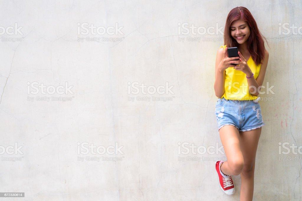 Mutlu genç güzel genç kız beton duvara gülümseyen portresi stok fotoğrafı