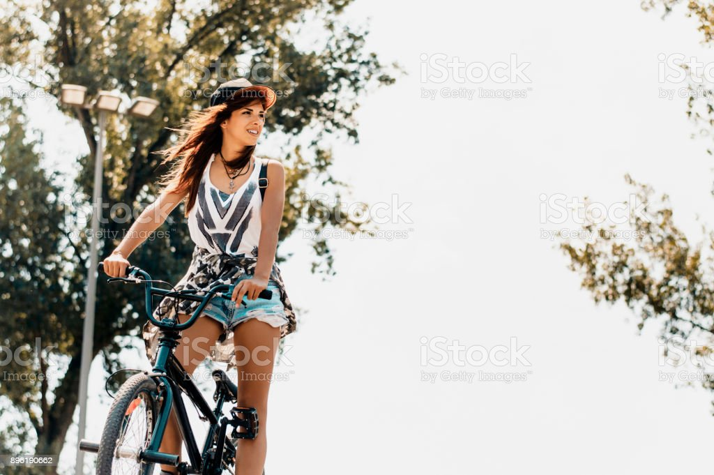 Portrait of happy young bicyclist riding in park. stock photo