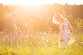 Portrait of happy young blond woman running on a meadow on a sunny summer day. Girl dancing on the grass in the park. Outdoors. Cheerful woman on sunset. Lifestyle and happiness concept
