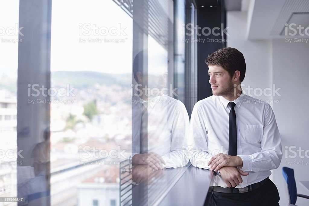 portrait of happy young business man at office standing over window