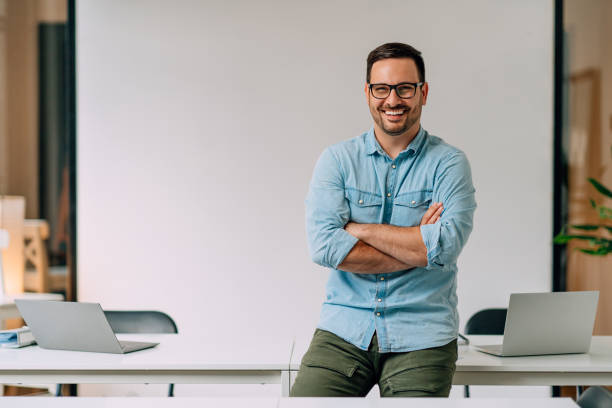 Portrait of happy young businessman at his office stock photo