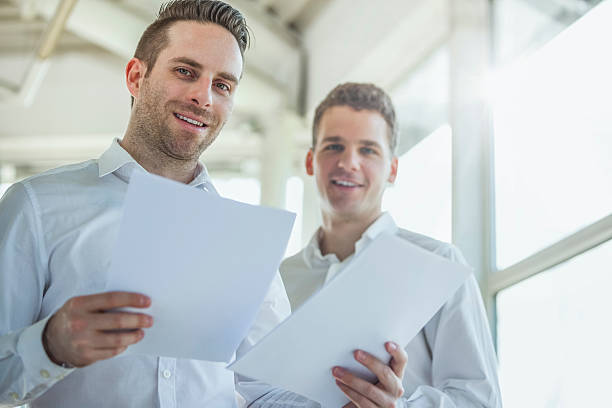 Portrait of happy young businessmen reviewing documents in office – Foto